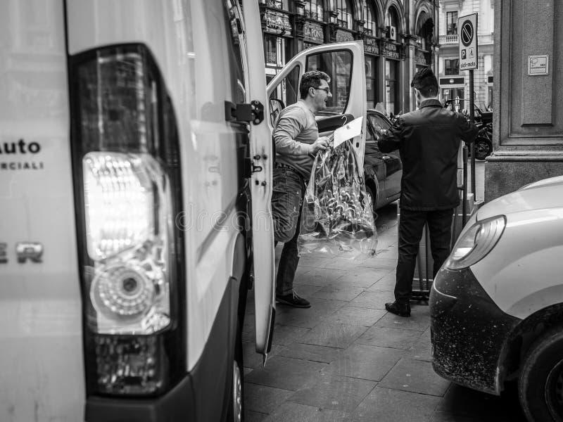 Milão, Itália - 23 de março de 2016: Trabalho de dois homens como as flores delive foto de stock