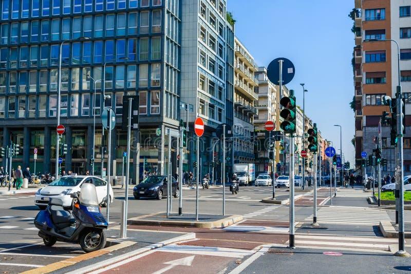 Milão, Itália - 19 de outubro de 2015: As estradas transversaas com lotes dos sinais e da estrada assinam dentro a cidade moderna fotografia de stock