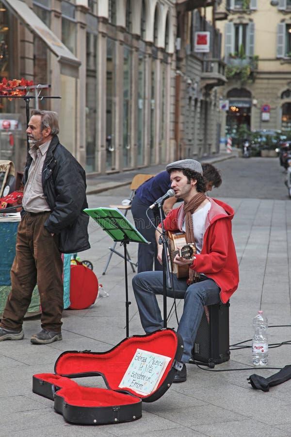 Milão, Itália - em maio de 2017: O músico da rua joga a guitarra e canta-a no microfone Outro um homem arranja o equipamento de s fotografia de stock