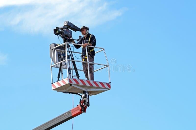 MILÃO, ITÁLIA -10 novembro de 2015: Operador cinematográfico que trabalha em uma plataforma de trabalho aéreo imagem de stock