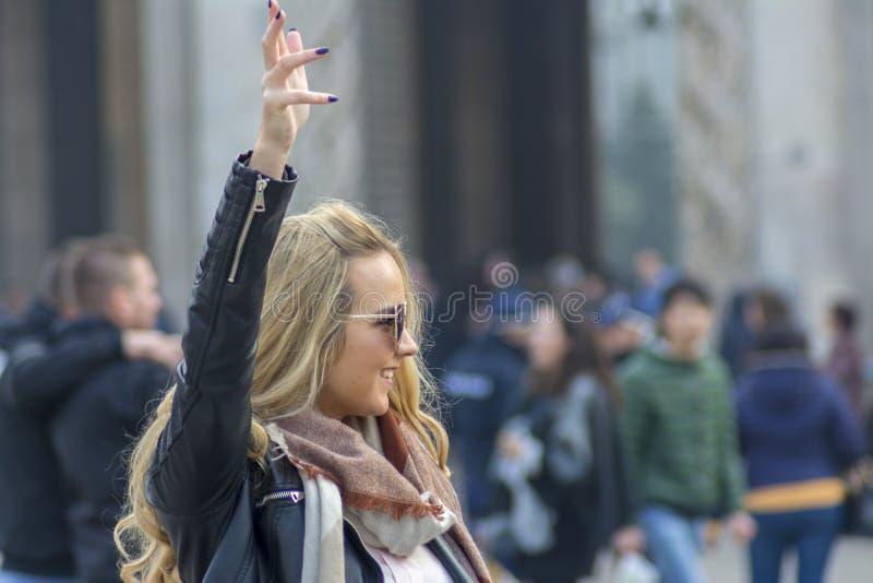 Milão, Itália 23-11-2017 Uma menina feliz no quadrado na frente de Milan Cathedral que chama um amigo imagem de stock royalty free