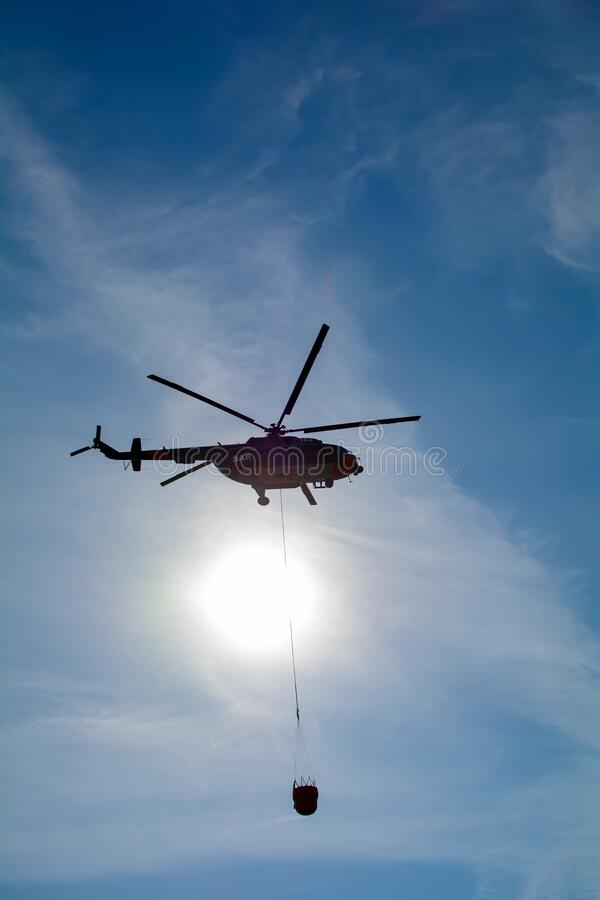 Free Mil Mi-17 Helicopter Flies In The Sky Carrying Bucket Of Water For Fire Fighting Purposes Stock Photos - 196716243