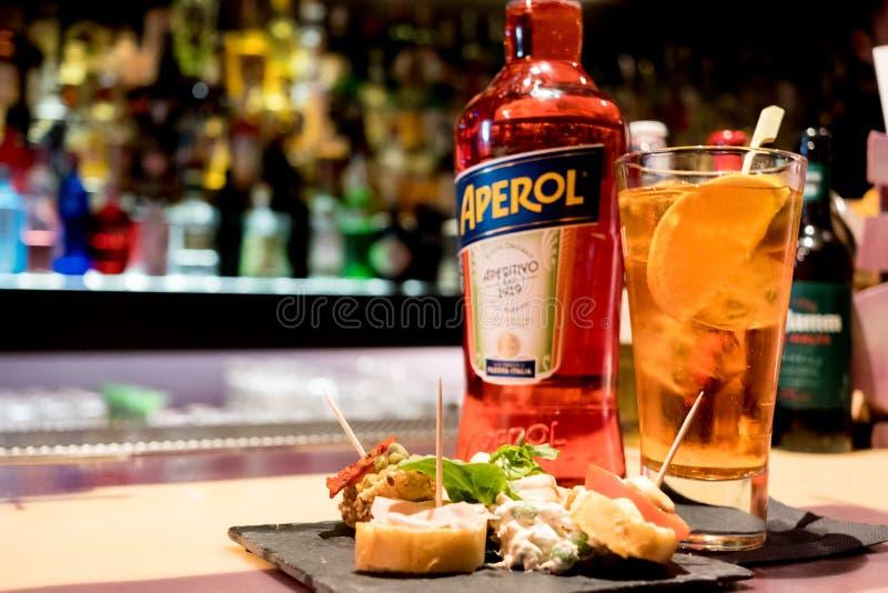 Milaan, Italië - 20 april 2019: fles van Italiaanse drankaperol spritz op barbovenkant met traditionele Italiaanse gelukkige uura stock afbeelding
