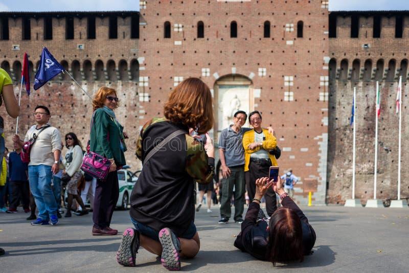 Milaan, Italië - September 28: De niet geïdentificeerde Aziatische toeristen maken foto's voor Castello Sforzesco op 28 September royalty-vrije stock afbeeldingen