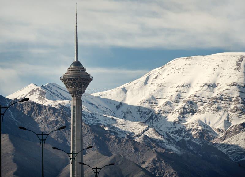 Milad Tower av Teheran av snö täckte framme Alborz berg arkivfoton