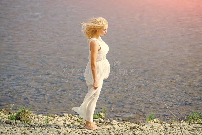Milagre da gravidez Mulher gravida no vestido branco que anda na praia do mar fotos de stock royalty free