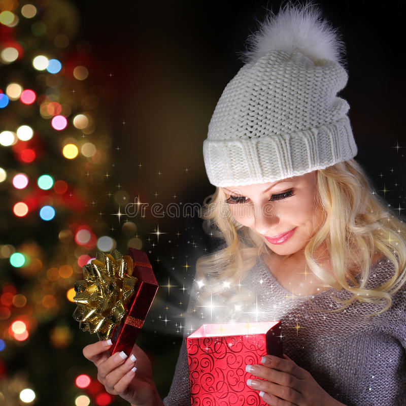 Milagro de la Navidad. Muchacha rubia sonriente con el sombrero hecho punto con la caja de regalo imagenes de archivo