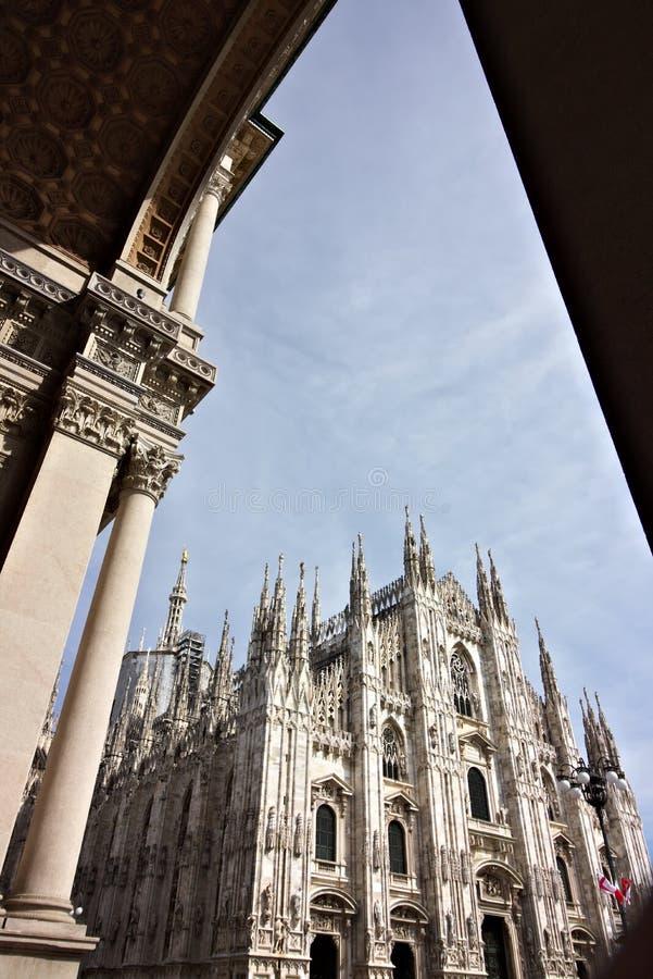 Milan Cathedral fasad med bl? himmel I f?rgrunden b?garna av portiken royaltyfri foto