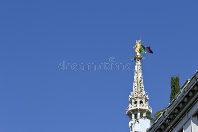 Milan Cathedral - The Madonnina with italian flag, golden statue on the highest gothic spire. Blue sky background, top landmark stock image