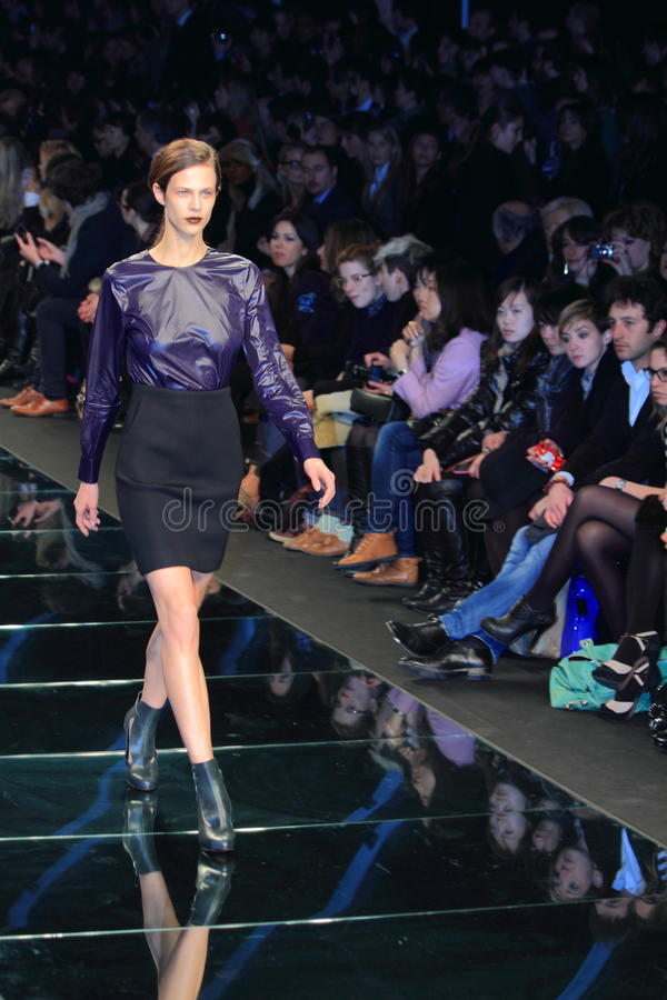 Milan catwalk fashion colinne michaelis. Model colinne michaelis on the catwalk showing the new summer spring collection, wearing a purple shirt and black skirt royalty free stock image