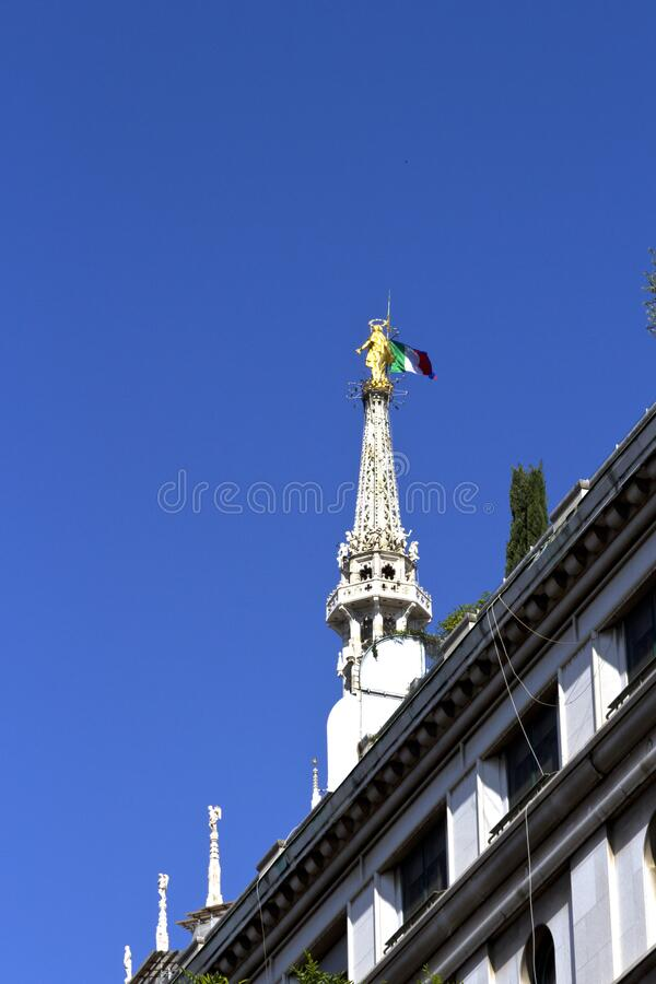 Milan Duomo Cathedral, view on golden statue of Madonna with italian flag placed on the highest gothic spire. Blue sky background, stock photography