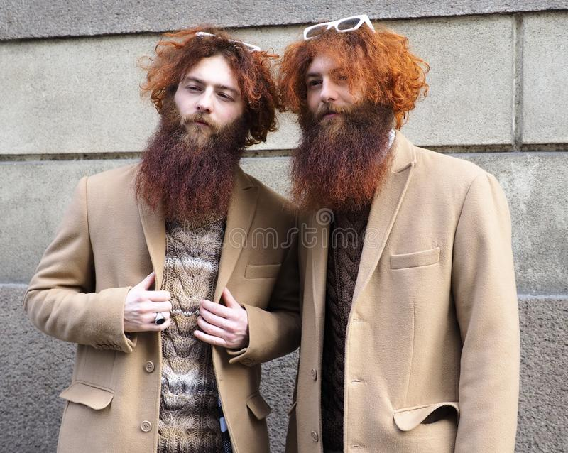 MILAN - FEBRUARY 24, 2018 Two fahionable twins posing for photographers after ERMANNO SCERVINO fashion show. royalty free stock photo