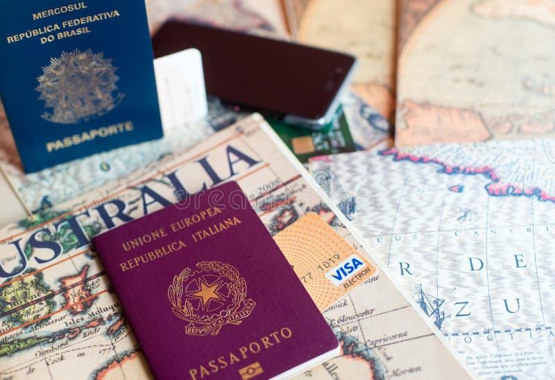 Milan Italien – Juli 20, 2018: En italienare och brasilian pass med en smartphone över en turist- tidskrift av Sydamerika och royaltyfri bild