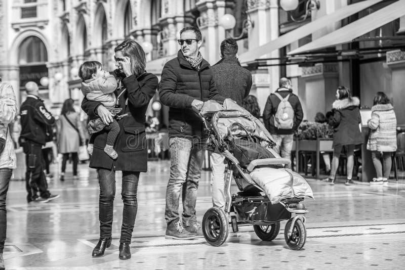 Milan Italien - mars 23, 2016: Den unga familjen med behandla som ett barn carri royaltyfri bild