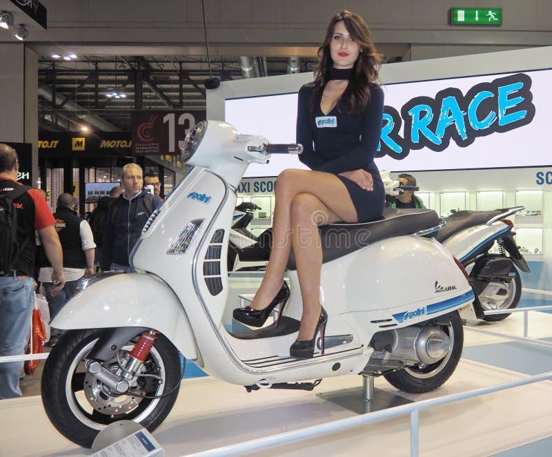 MILAN ITALIEN - NOVEMBER 9: Modellen poserar på mopeden på EICMA, internationell motorcykelutställning på NOVEMBER 9, 2017 arkivbild