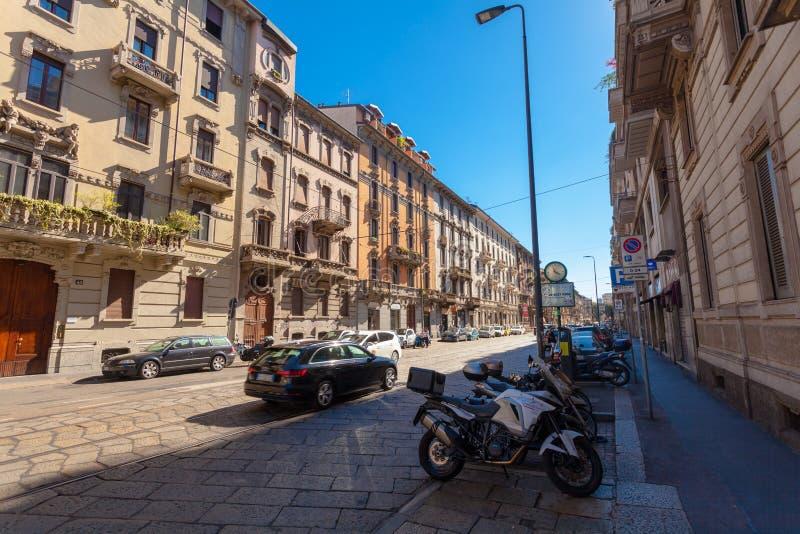 MILAN ITALIEN - September 06, 2016: Bilar och parkerade motorcyklar och sparkcyklar på gatan via Luigi Settembrini arkivbilder