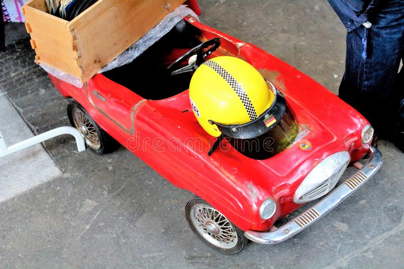 Milan, Italy - April 23, 2017: pedal car red toy 50s-60s with yellow helmet at a vintage market. Milan, Italy - April 23, 2017: evocative image of a red toy 50s stock photography