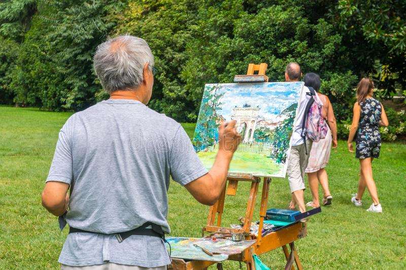 Milan, Italy - 14.08.2018: artist draws Arch of Peace in Sempione Park royalty free stock images