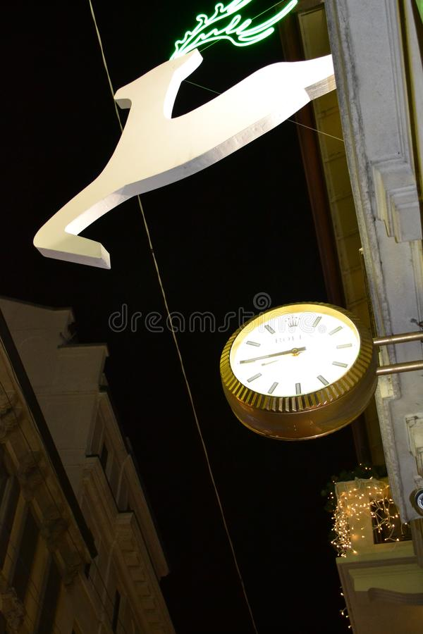 Running white deers and the street golden clock of the Rolex boutique decorated for the Christmas holidays. stock image