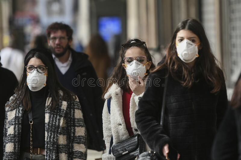 Coronavirus emergency in Milan. Milan, Italy - February 23, 2020: Coronavirus emergency in Milan, citizens and tourists stroll through the city center wearing