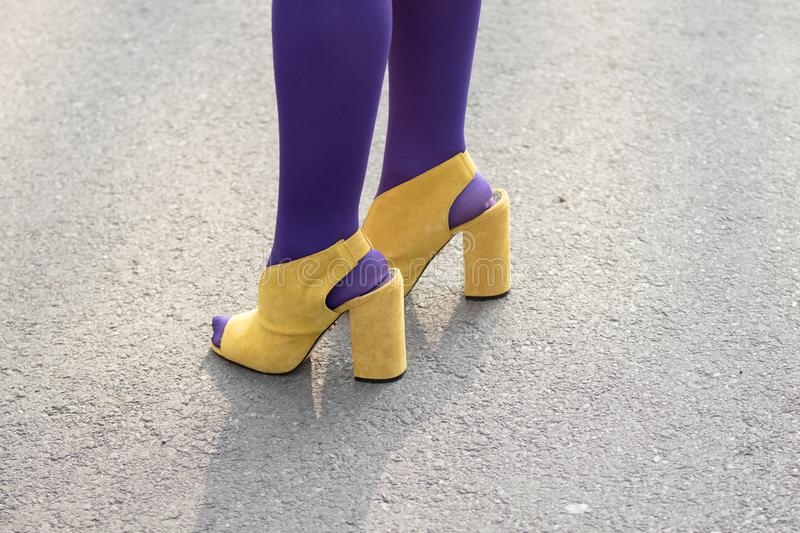Model wears a pair of yellow shoes with heels and purple socks stock images
