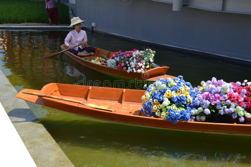 Hostess of the Thailand pavilion of the EXPO Milano 2015 is sitting in a traditional Thai wooden boat filled with heap of flowers. royalty free stock photos