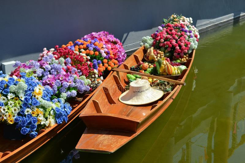 Two Thai wooden traditional boats for floating market filled up with flowers at the Thailand pavilion of the EXPO Milano 2015. royalty free stock image