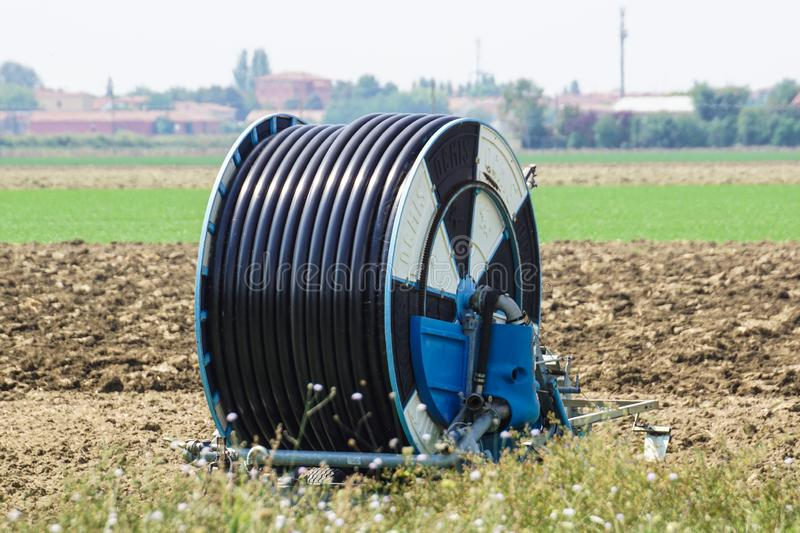Milan , italy , 17 march 2018 : Agricultural equipment. Hose reel, pump and sprinkler for irrigation on a rye field stock photography