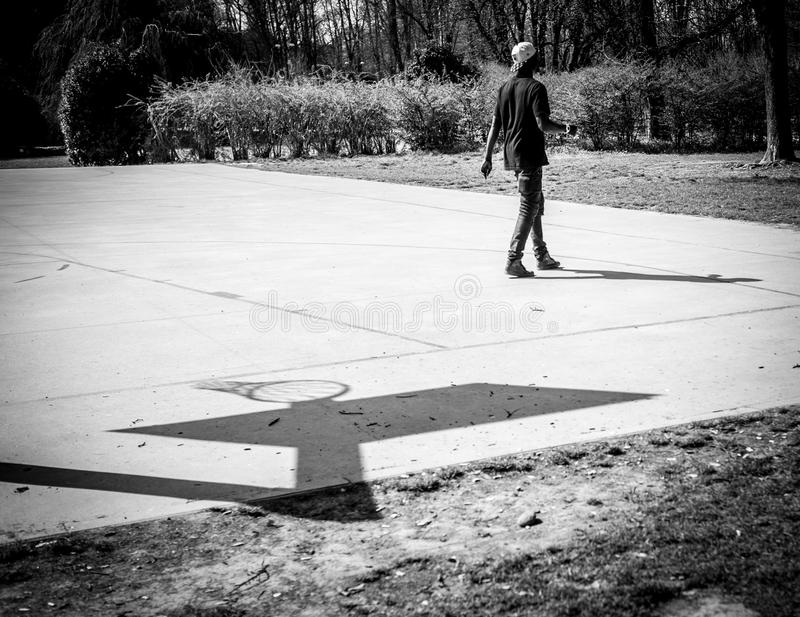 Milan, Italy - March 23, 2016: black man player on the basketba. Ll Basketball court at Sempione Park Parco Sempione in Milan, Italy royalty free stock photo