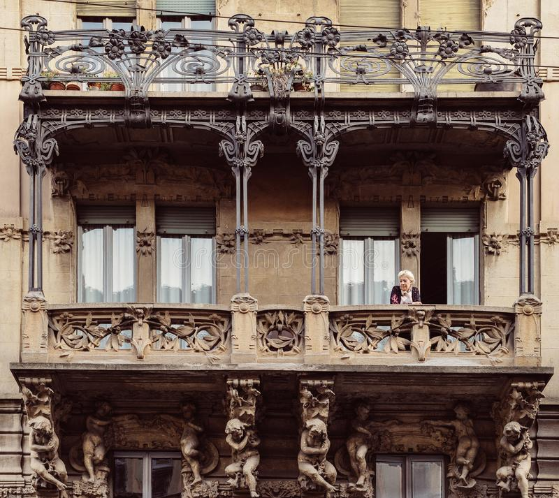 Older woman on balcony of typical residential palace at Milan`s Porta Venezia neighbourhood royalty free stock photography