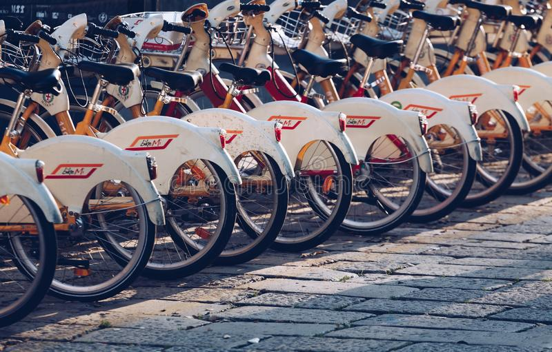 Milan Italy NOV 2018 rental city bikes parked in a row on the square - Bike sharing system stock images