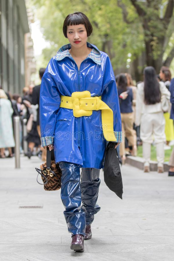Asian model wearing a pair of blue polishing rubber trousers an electric blue coat in shiny rubber with a striking yellow belt stock photos