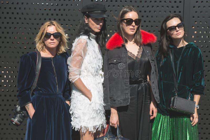 Fashionable women posing during Milan Women`s Fashion Week. MILAN, ITALY - SEPTEMBER 20: Fashionable women pose outside Gucci fashion show building during Milan stock photography