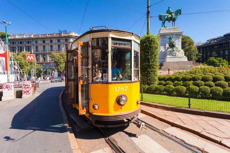 MILAN, ITALY - September 07, 2016: The old yellow tram has stopped and opened doors on the tram stop near metro station Cairoli wh stock image