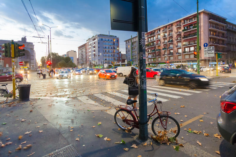 MILAN, ITALY - September 06, 2016: Red colored bicycle parked fastened by lock to the street pole in Milana stock image