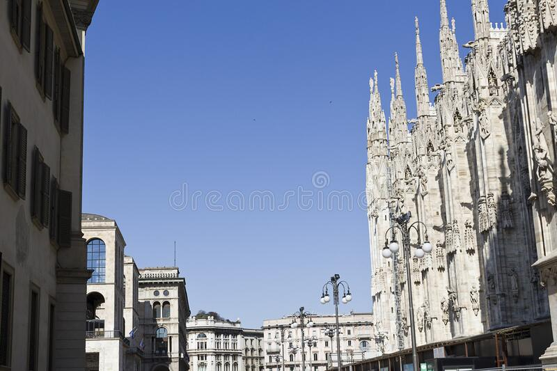 Milan piazza del Duomo -  perspective on side of gothic Cathedral and historic buildings exterior of the square. Blue sky royalty free stock photos