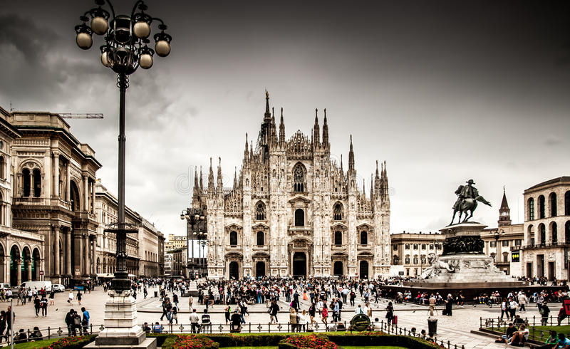 Miland Cathedral. A view of Milan Cathedral fromthe front, including the large square filled with people in front of it, and some buildings to the side royalty free stock image
