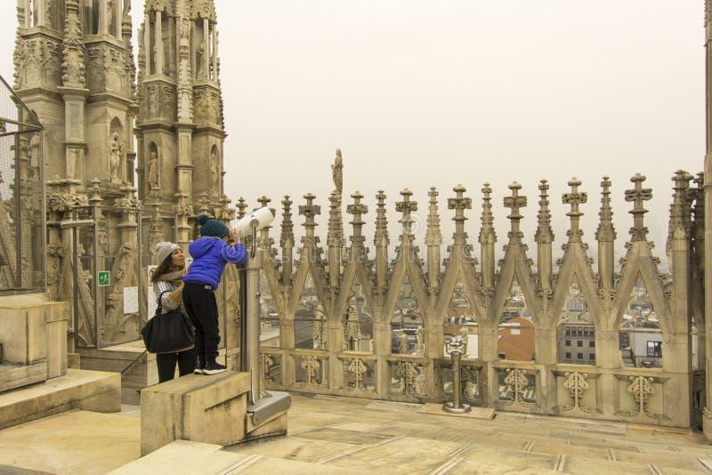 Milano, Italia, il 24 novembre 2017 Sul tetto dello sguardo della madre e del bambino di Milan Cathedral tramite un telescopio fotografia stock libera da diritti