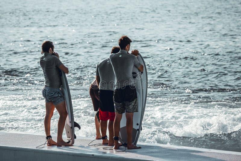 MIlano Italien, 20 juni, 2019/grupp av unga surfare med bränningbräden som väntar på deras vänd i vågpölen Idroscalo sjö arkivfoto