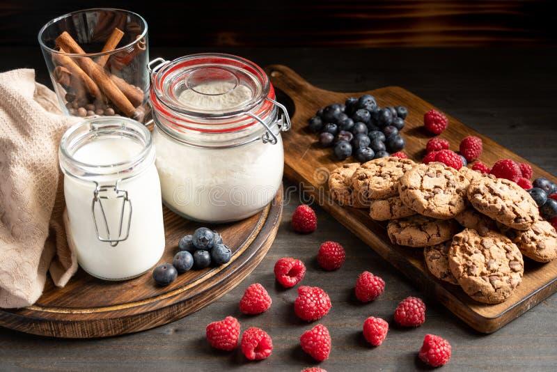 Milch, cinnamom, Mehl in Siegelgläsern, Kekse und Beeren gesetzt auf Holz lizenzfreies stockfoto