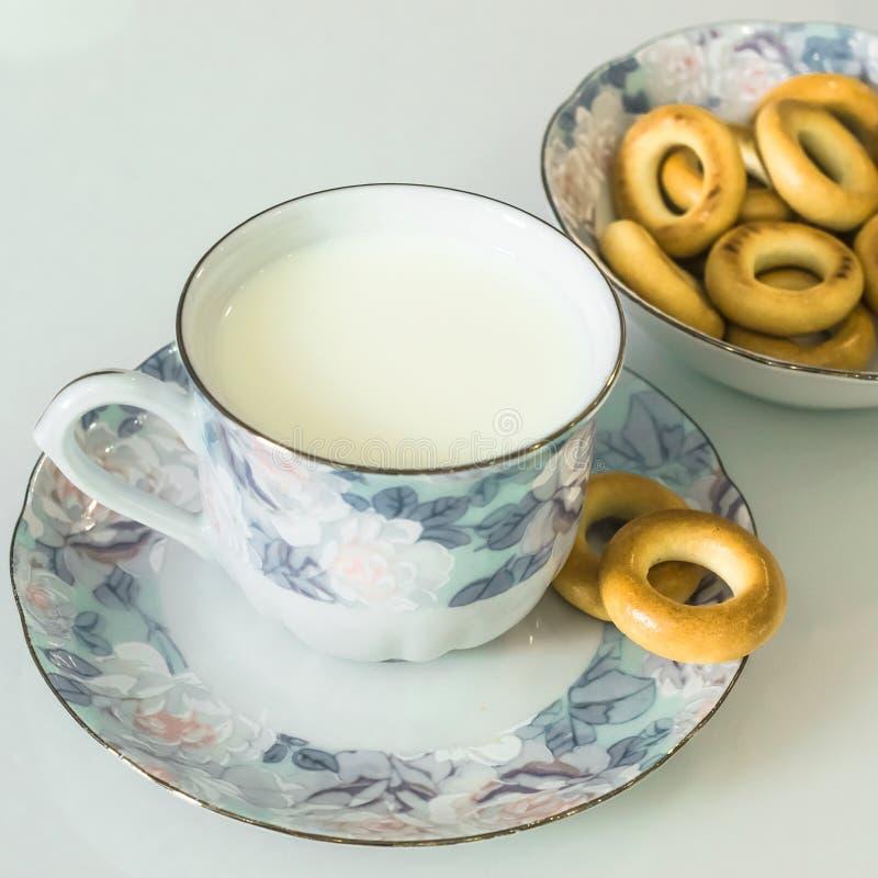 Milch in einem Becher auf dem Tisch mit dem Brot, trocknend stockfotos