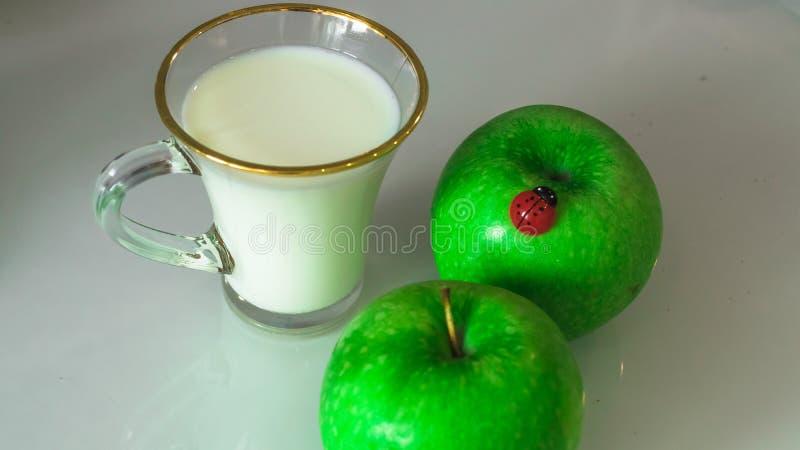 Milch in einem Becher auf dem Tisch mit dem Brot, trocknend lizenzfreies stockfoto