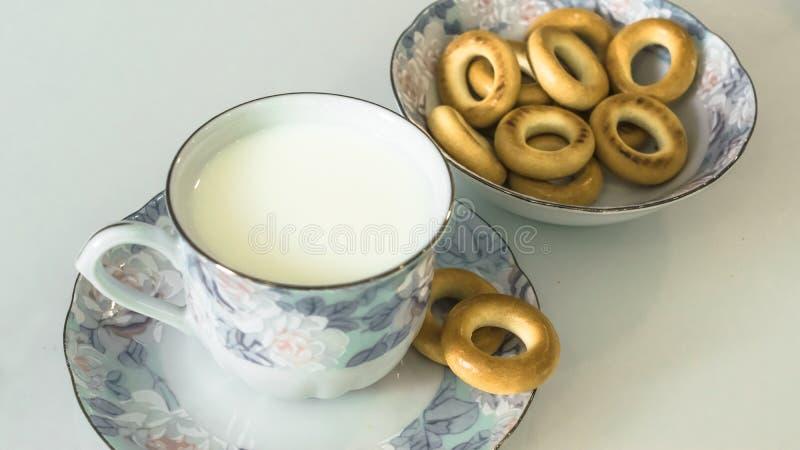 Milch in einem Becher auf dem Tisch mit dem Brot, trocknend lizenzfreie stockbilder