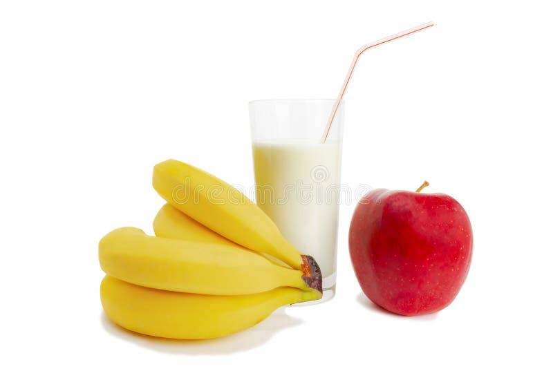 Milch in einem Glas, in den Bananen und in einer Apfellüge nahe bei alles auf einem weißen Hintergrund stockfoto
