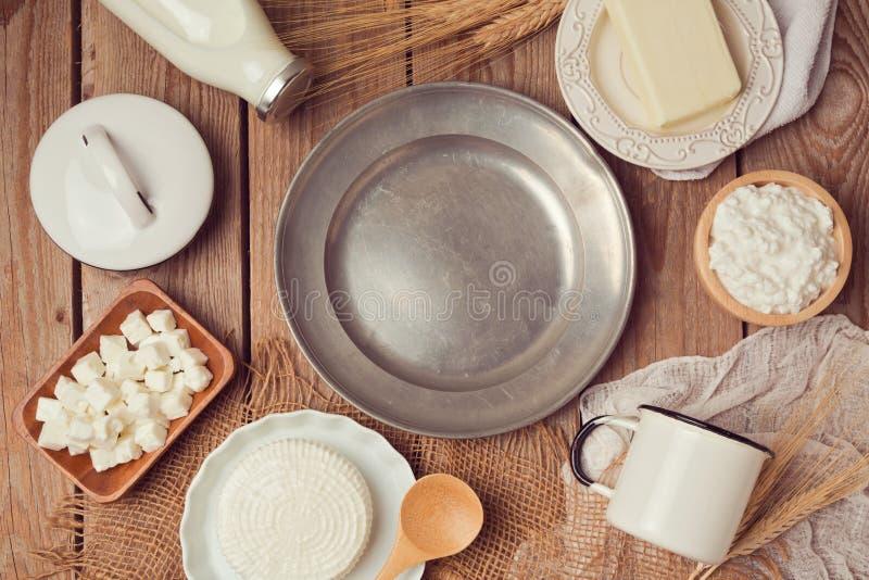 Milch, Käse und Butter um leere Weinleseplatte auf Holztisch Gesundes Essenkonzept Ansicht von oben lizenzfreies stockbild