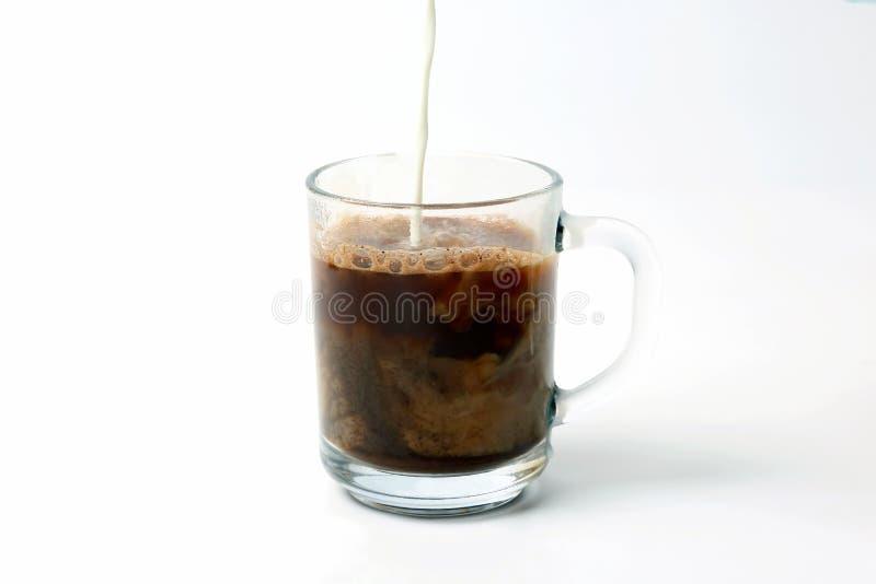 Milch lief in eine transparente Schale schwarzen Kaffee aus stockfotografie