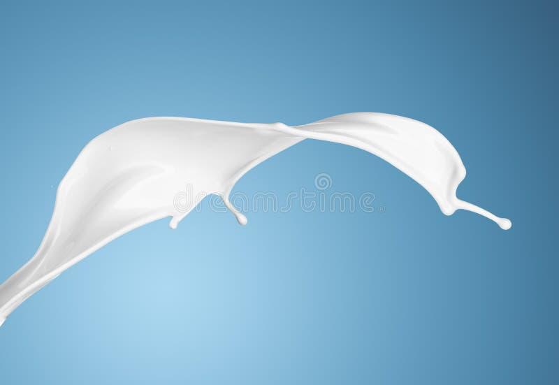 Milch oder weißes flüssiges Spritzen auf blauem Hintergrund lizenzfreie stockbilder