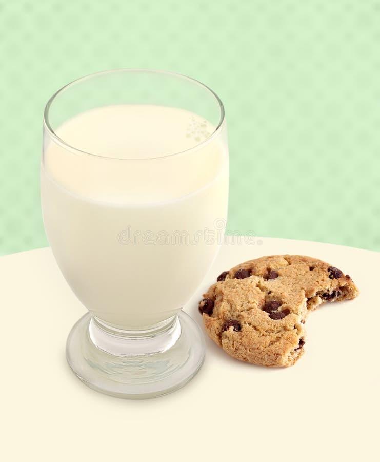 Milch u. Plätzchen mit dem Bissen genommen auf grünem Hintergrund stockbilder