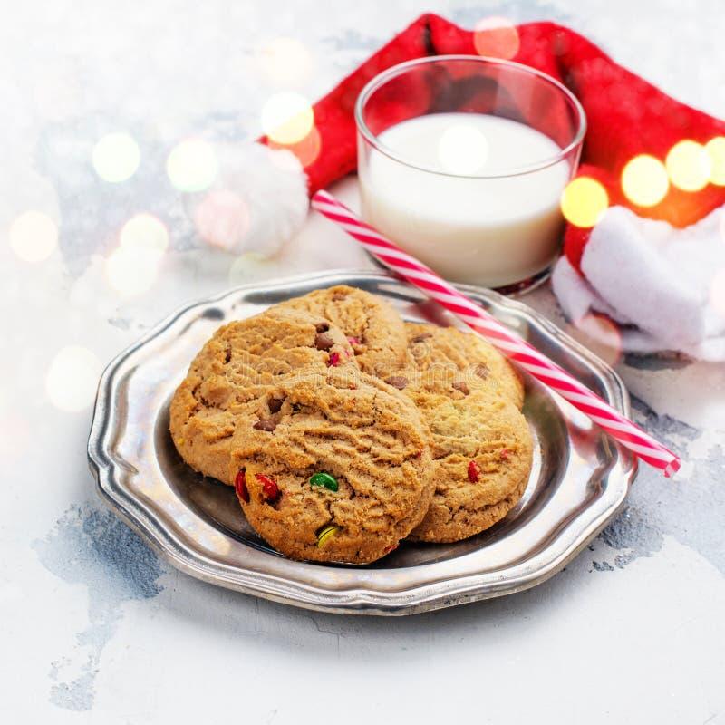 Milch und Plätzchen für Santa Claus- und Sankt-` s Hut über hölzernem BAC lizenzfreie stockbilder