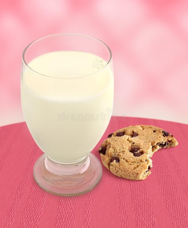 Milch und Plätzchen mit dem Bissen genommen - rosafarbener Hintergrund stockfotografie